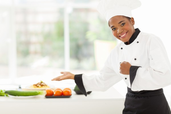 cheerful african female chef presenting vegetables
